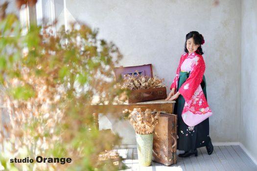 奈良市のフォトスタジオ、スタジオオレンジで撮影。赤ベースの着物と合う深い緑の袴で記念撮影。
