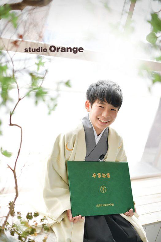 奈良市のフォトスタジオ、スタジオオレンジで小学校卒業の記念撮影。太陽の光が入る大きな窓の側で袴姿で卒業証書と。