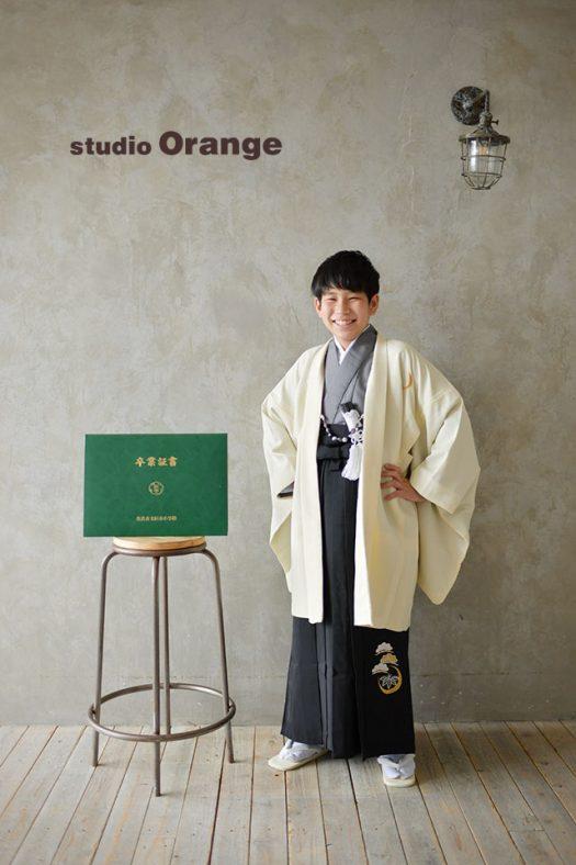 奈良市の写真館、スタジオオレンジで小学校卒業の記念撮影。生成りの羽織と墨色の袴で卒業証書を傍に笑顔で撮影。
