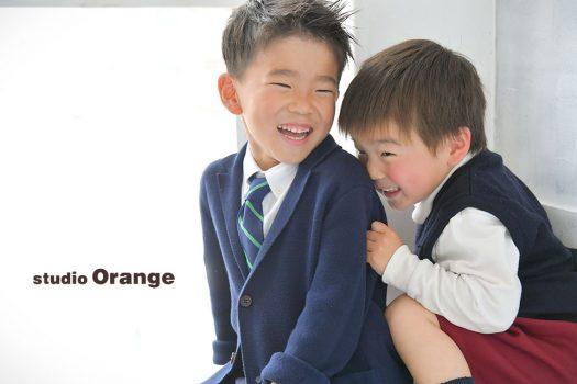 奈良市のフォトスタジオ、スタジオオレンジで撮影。恥ずかしさで兄の背中に隠れる弟と、それを見て笑うお兄ちゃん。