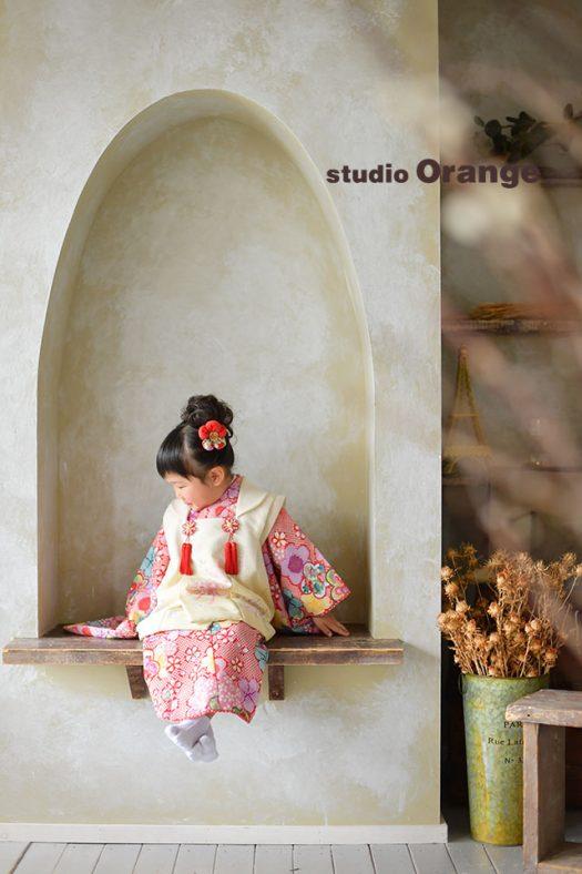 奈良市のフォトスタジオ、スタジオオレンジで七五三前撮り撮影。赤い着物の3歳女の子、お袖を見るふとした瞬間を撮影。