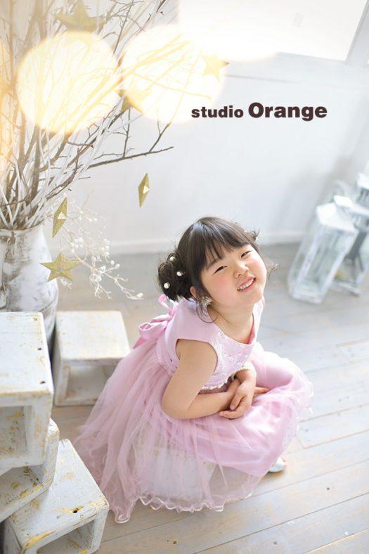 奈良市のフォトスタジオ、スタジオオレンジで撮影。ピンクのドレスを着てカメラを見上げる女の子。