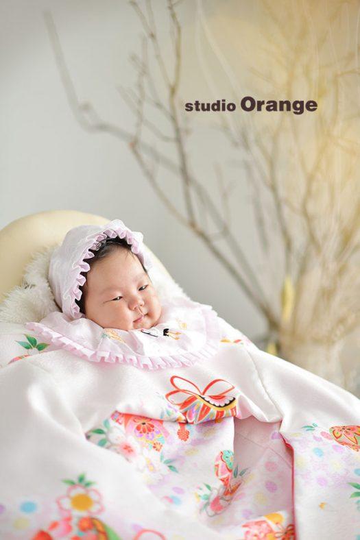 奈良市のフォトスタジオ、スタジオオレンジで女の子のお宮参り撮影。白い産着と太陽の光が暖かく、うっとりした表情の赤ちゃん。