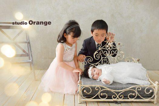 奈良市のフォトスタジオ、スタジオオレンジでお宮参り撮影。ベビードレスの妹をじっと見つめるドレス姿のお姉ちゃんと、スーツを着たお兄ちゃん。