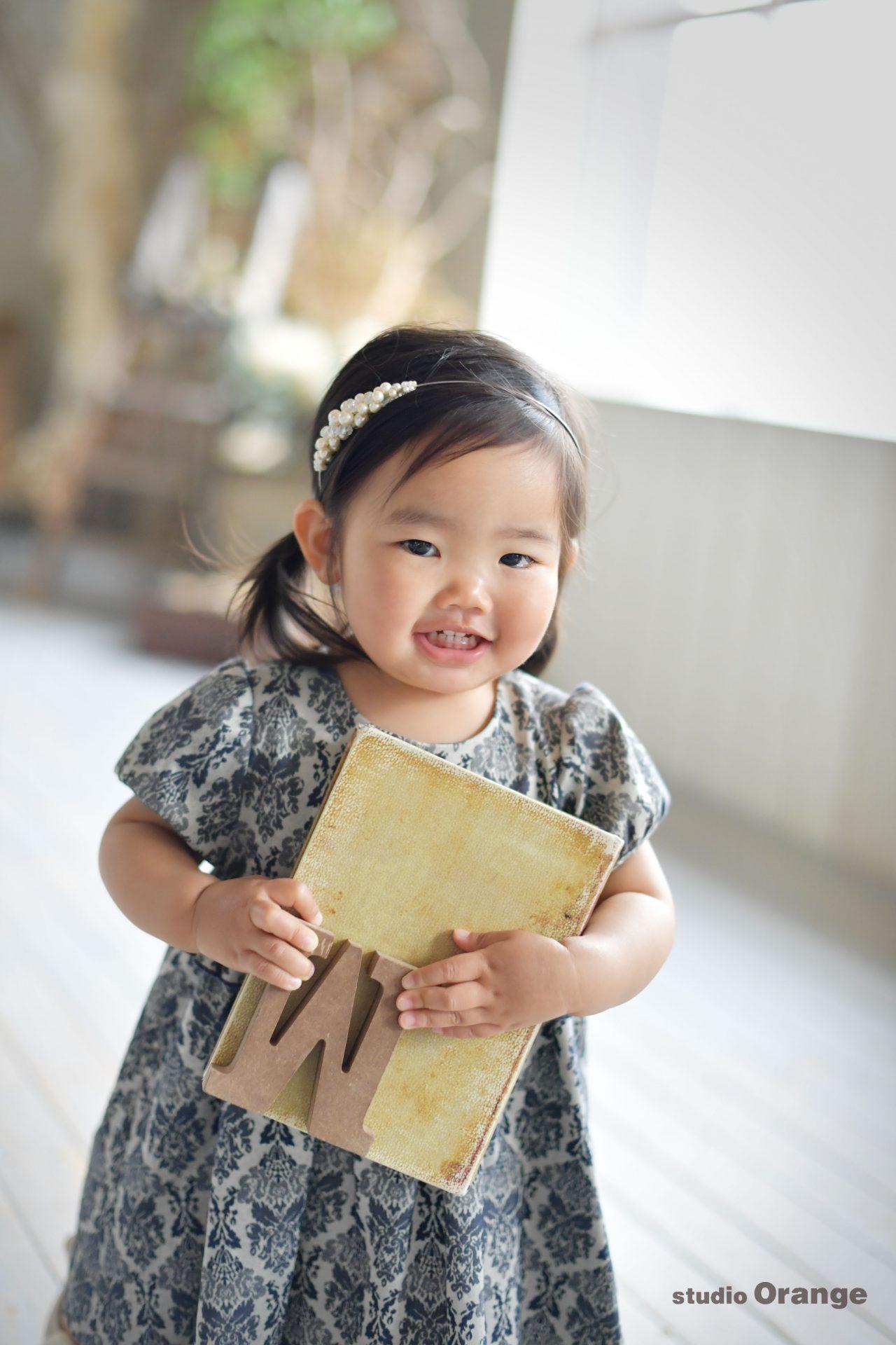 奈良市のフォトスタジオ、スタジオオレンジでバースデー撮影。スタジオで見つけたお気に入りおおもちゃを大事に抱えるドレスを着た女の子。