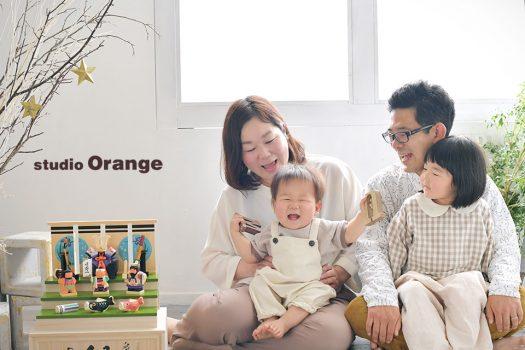 奈良市のフォトスタジオ、スタジオオレンジで端午の節句撮影。お持ち込みの木彫りの兜と一緒に私服でカジュアルな家族撮影。