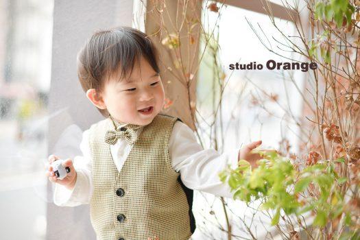 奈良市のフォトスタジオ、スタジオオレンジでバースデー撮影。ベスト風ロンパースでお気に入りのおもちゃを握りしめながら遊ぶ姿。