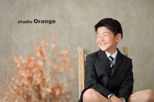 奈良市のフォトスタジオ、スタジオオレンジで撮影。スタジオのスーツを着て恥ずかしながらも良い笑顔で撮影。