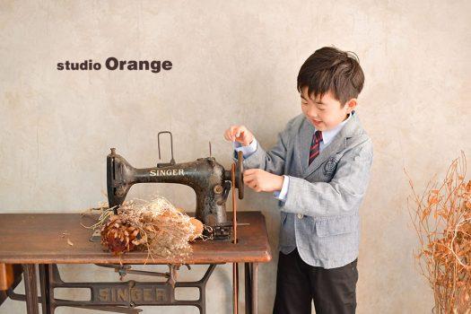 奈良市のフォトスタジオ、スタジオオレンジで撮影。スタジオの衣装を着て、SINGERのアンティークミシンに興味津々な姿。