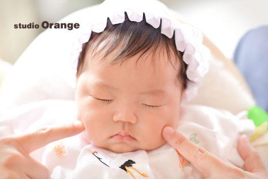 奈良市のフォトスタジオ、スタジオオレンジでお宮参りの記念撮影。お1人撮影中に眠ってしまいパパママに頬をつつかれる赤ちゃん。