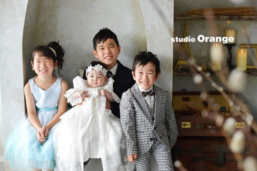 奈良市のフォトスタジオ、スタジオオレンジでお宮参り撮影。お兄ちゃんの抱っこでベビードレス姿を兄妹4人でご撮影。
