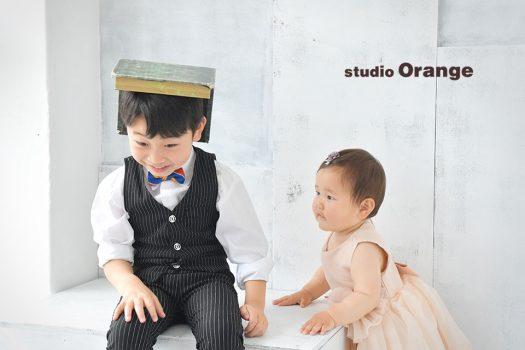 奈良市の写真館スタジオオレンジ奈良店で撮影。洋装の2ショット撮影で楽しそうなお兄ちゃんを真顔で見つめる1歳妹。