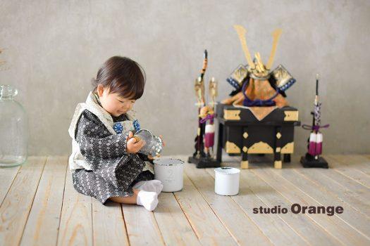 奈良市のフォトスタジオ 、スタジオオレンジで端午の節句撮影。お被布を着ておもちゃで遊ぶ姿を兜と一緒に撮影。