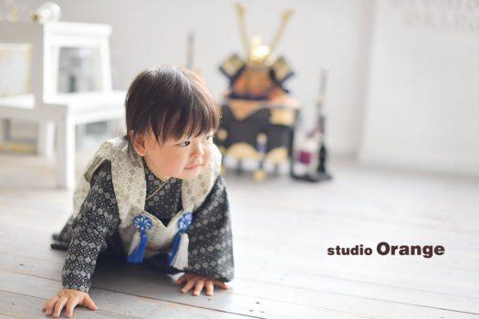 奈良市のフォトスタジオ 、スタジオオレンジで初節句の記念撮影。初めて袖を通す着物で兜と一緒にはいはい姿を撮影。
